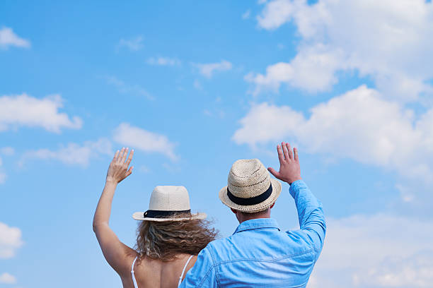 Back view of couple waving hands to the sky